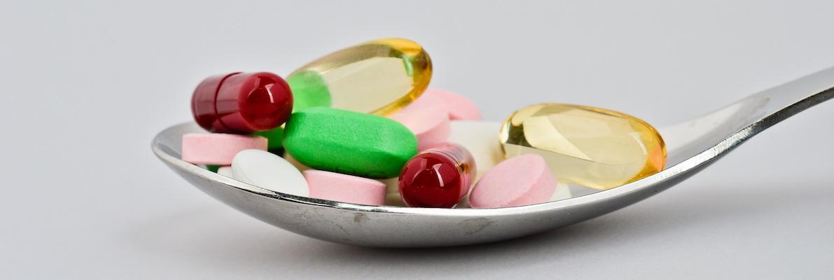 Wirksamkeit in der Suchtberatung - Vortrag Prof. Dr. Schellberg. Löffel mit Tabletten.